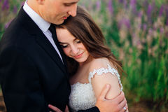 Pleasing bride leans to groom& x27;s chest while he hugs her tenderly Royalty Free Stock Photography