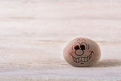 Pleasing emoticon. Stone face on white wood background with free space for your text stock images