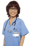 Pleasing female gynecologist posing. Pleasing matured asian female gynecologist with stethoscope around her neck Stock Photography