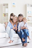 Pleasure. A happy family with children on a white sofa at home Royalty Free Stock Image