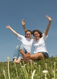 Pleasure. Two nice young girls sit on a grass on a background of the blue sky, smile and wave hands Stock Photography