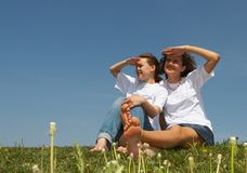 Pleasure 3. Two nice young girls sit on a grass on a background of the blue sky, smile and wave hands Stock Photography