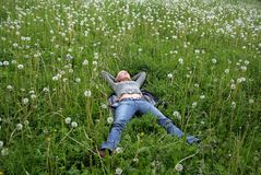 Pleasure. To roll in a floor of dandelions and to look at the sky Royalty Free Stock Photo