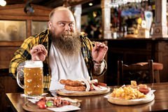Pleasure bearded man eating food in boozer Stock Photos