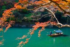 Pleasure boat at Arashiyama in Autumn season. The famous ways to explore Arashiyama is by renting a boat stock image