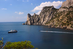Pleasure boat in the bay.Crimea. Pleasure boat,blue bay and sheer cliffs Stock Photos