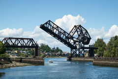 Pleasure boat below raised drawbridge. Seattle, USA July 20, 2016: Small pleasure boat passing below raised drawbridge. Salmon Bay drawbridge for BNSF railroad Stock Images