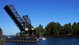 Pleasure boat cruises towards  railroad bridge Stock Photography