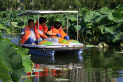 Pleasure boat driving slowly in the water, in a park Stock Photos
