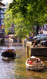 Pleasure boat floats on the channel in Amsterdam, the Netherlands. royalty free stock images