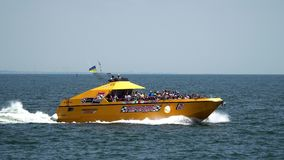 Pleasure boat floats with people in front of camera stock video