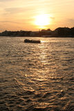 Pleasure boat floats on the river at sunset Stock Photography