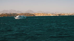 Pleasure Boat Floats on the Waves of the Red Sea on the Background of Coast and Beaches in Egypt. Ship moves on the high seas against the backdrop of mountains stock video