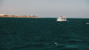 Pleasure Boat Floats on the Waves of the Red Sea on the Background of Coast and Beaches in Egypt stock video