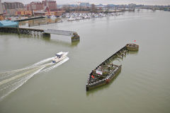 Pleasure Boat Navigates River Swing Bridge. High angle view of a pleasure boat navigating through the opening of a swing bridge crossing a river Stock Photos