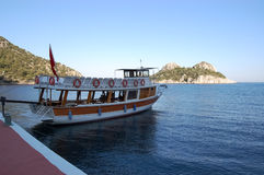 Pleasure boat near the pier on the shores of a blue lagoon. Pleasure boat near the pier on the shores of a blue lagoon in the Aegean Sea in Turkey Stock Images