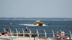 Pleasure boat with people floats near the beach stock video