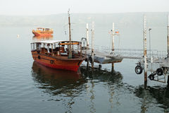 Pleasure boat at the pier. TIBERIAS, ISRAEL - FEBRUARY 27, 2017: Pleasure boat at the quay on the Kinneret lake on a misty morning Stock Photography