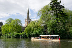 Pleasure boat on the River Avon. A pleasure boat on the River Avon in Stratford upon Avon. Church of the Holy Trinity in the background, is where William Stock Photography