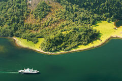 Pleasure boat ship are sailing between fjords. Amazing nature of the Norwegian mountains in Sognefjord. Royalty Free Stock Image