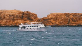Pleasure boat with tourists is sailing in the storm sea on background of rocks. Egypt stock footage