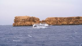 Pleasure boat with tourists is sailing in the storm sea on background of rocks. Egypt. Sharm El Sheikh. Bad weather at sea. Slow Motion in 180 fps. View from stock video