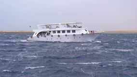Pleasure Boat with Tourists is Sailing in the Storm Sea. Egypt, Sharm El Sheikh. Bad weather at sea. Slow Motion in 180 fps. View from the ship. Boat trip in stock footage