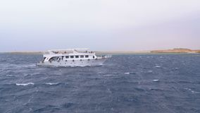 Pleasure Boat with Tourists Sails in the Stormy Sea on the background of Rocks. Egypt. Pleasure Boat with Tourists Sails in the Storm Sea on the background of stock video footage