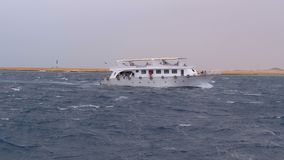 Pleasure boat with tourists sails in the stormy sea on the background of rocks. Egypt. Slow Motion. Pleasure boat with tourists sails in the storm sea on the stock video