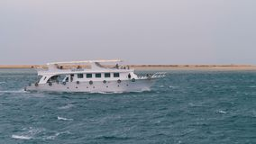 Pleasure boat with tourists sails in the stormy sea on the background of rocks. Egypt. Pleasure boat with tourists sails in the storm sea on the background of stock video