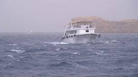Pleasure boat with tourists sails in the stormy sea on the background of rocks. Egypt stock footage