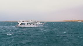 Pleasure boat with tourists sails in the stormy sea on the background of rocks. Egypt stock video