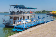 Pleasure boat waiting for passengers on an embankment Stock Photography