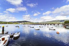 Pleasure boats anchored in the Eume river on the Atlantic coast. And stone bridge that crosses with mountains in the background and sky with some clouds in La Stock Photography