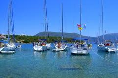 Pleasure boats in blue sea water. Beautiful yachts anchored in transparent clear water of Ionian Sea,Fiskardo bay marina,Kefalonia island,Greece Stock Photo