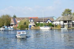 Pleasure boats  on  River Yare centre for tourism on Norfolk Broads with houses  in background Stock Images