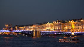 Pleasure boats sail under the palace bridge in St. Petersburg at night. In the background, the Hermitage stock video