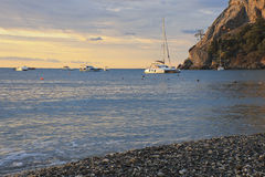 Pleasure boats and yachts in a rocky bay at dawn. Pleasure boats and yachts in a rocky bay of the Black Sea coast at dawn stock images
