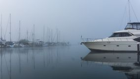 Pleasure craft on a cold, misty morning. A pleasure craft / boat sitting on glassy-still waters within a misty morning harbor royalty free stock images
