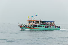 The pleasure craft with passengers onboard under the flag of Thailand floats Stock Photo