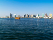 Pleasure Dhow on Dubai Creek. A pleasure dhow for tourist crusing up the Dubai Creek whose banks are lined more dhows and packed with modern high rise office Royalty Free Stock Photo