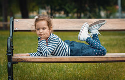 Pleasure little girl lying on bench Royalty Free Stock Photos