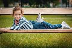Pleasure little girl lying on bench Stock Image