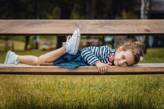Pleasure little girl lying on bench in a park Stock Photography