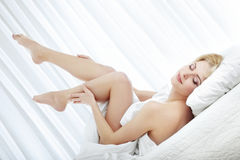 Pleasure at the morning. Elegant lady with naked legs laying on the bed at the morning Royalty Free Stock Image