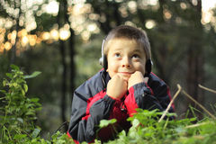 Pleasure of music. Boy in forest listening music in headphones with pleasure expression Royalty Free Stock Photography