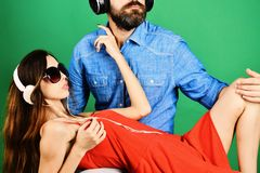 Pleasure, music and fun creative lifestyle concept. Music fans. With serious faces enjoy music. Mans face with beard holds girl lying on green background stock image