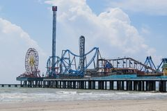Pleasure Pier on Galveston Island, Texas extends out into the Gulf of Mexico. Pleasure Pier on Galveston Island in Texas reaches across the ocean beach and out royalty free stock photos