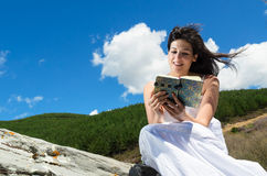 Pleasure of reading. Young woman enjoys reading her book in a sunny day outdoors Royalty Free Stock Photos