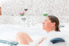 Pleasure of relaxation in the bath with foam Royalty Free Stock Images